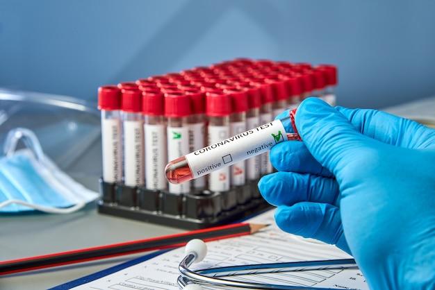 Ein reagenzglas in der hand mit negativen blutproben für covid-19 neben dem coronovirus-testformular.