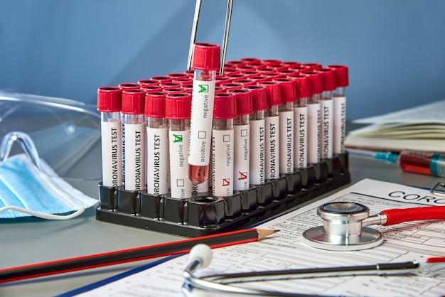 Ein reagenzglas in einer pinzette mit negativen blutproben für covid-19 neben dem coronovirus-testformular.
