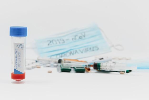 Ein reagenzglas mit einem positiven test für das cavid-2019-coronavirus. medizinische geräte auf einem weißen tisch. thermometer, phonendoskop, tabletten, operationsmasken