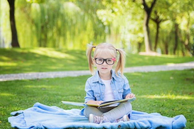 Ein recht kleines blondes mädchen mit dem blonden haar und lesebrille ein buch auf einem park lesend