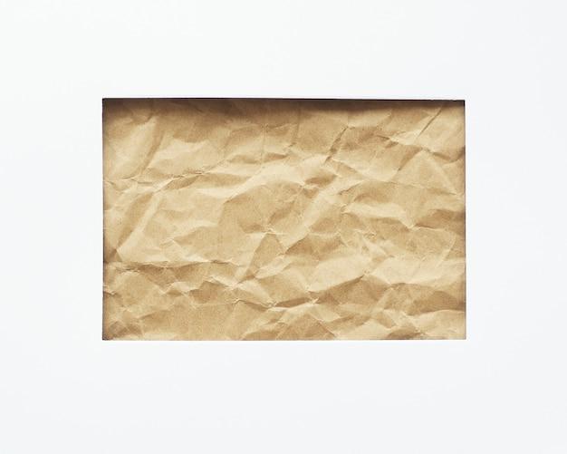 Ein rechteckiges loch in einem weißen blatt papier. zerknittertes bastelpapier im hintergrund. platz zum kopieren.