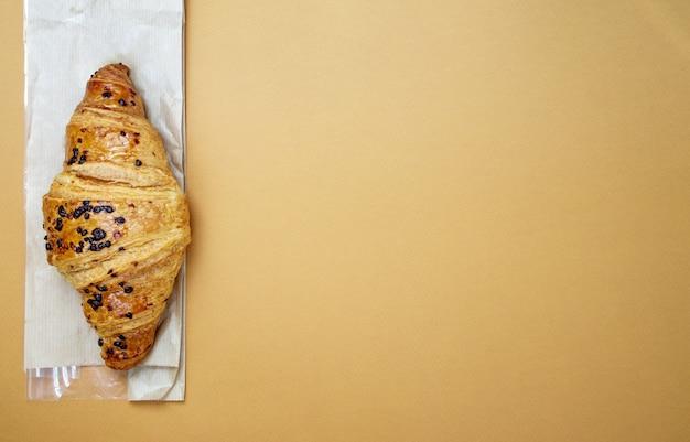 Ein regelmäßiges frisches knuspriges vollkorncroissant mit schokoladenfüllung auf braunem oder kaffeehintergrund mit kopienraum. klassisches traditionelles frisch gebackenes französisches dessert, gebäck. ansicht von oben, flach.