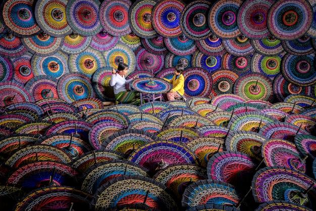 Ein regenschirmhersteller stellt traditionelle burmesische regenschirme her. bunte regenschirme am straßenmarkt in bagan, myanmar (burma). burmesische regenschirme