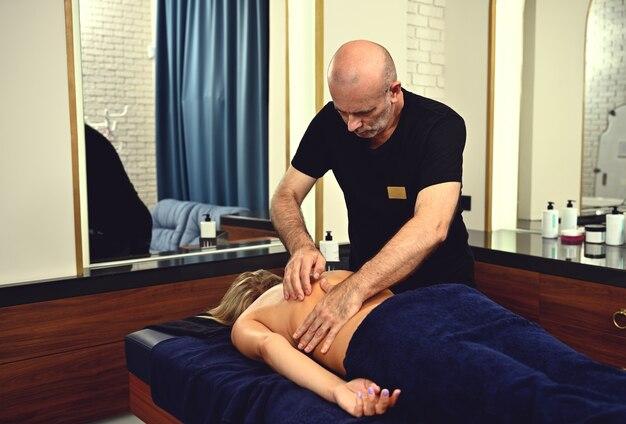 Ein reifer chiropraktiker gibt einem kunden des spa-zentrums eine therapeutische massage. professioneller masseur massiert den rücken einer frau in einer medizinischen spa-klinik