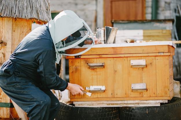 Ein reifer imker arbeitet an einem bienenstock in der nähe der bienenstöcke. natürlicher honig direkt aus dem bienenstock.
