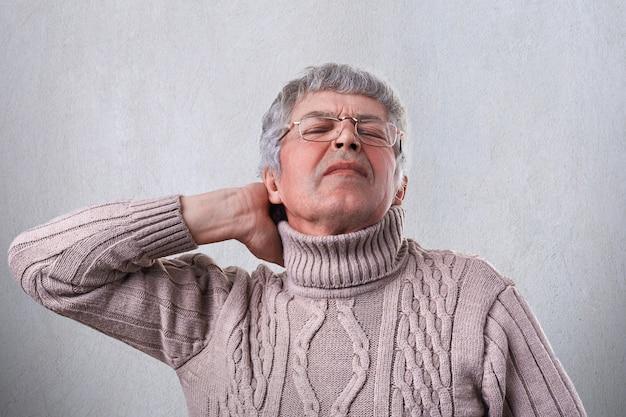 Ein reifer mann, der warmen pullover und eine brille trägt, die seine hand auf dem hals hält, der nach der arbeit im garten müde ist
