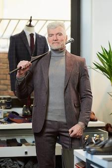 Ein reifer mann mit grauen haaren und sportlichem körperbau hält in einem bekleidungsgeschäft zwei schwarze papiertüten mit einkäufen und einen kohlefaserstock auf der schulter. eine kundin mit bart in einer boutique