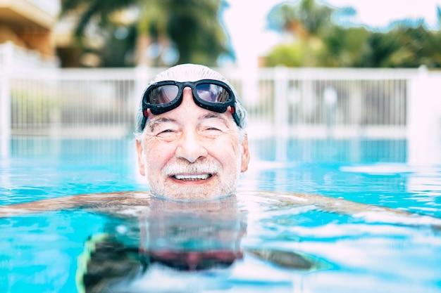 Ein reifer mann oder senior am pool, der lächelnd in die kamera schaut und allein spaß hat - gesunder und fitness-lifestyle