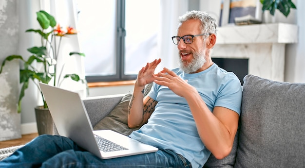 Ein reifer mann sitzt zu hause mit einem laptop auf dem schoß auf der couch und telefoniert.