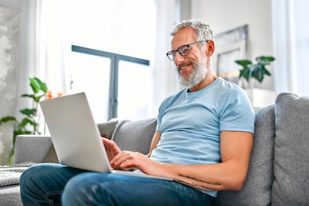 Ein reifer mann sitzt zu hause mit einem laptop auf dem schoß auf der couch.