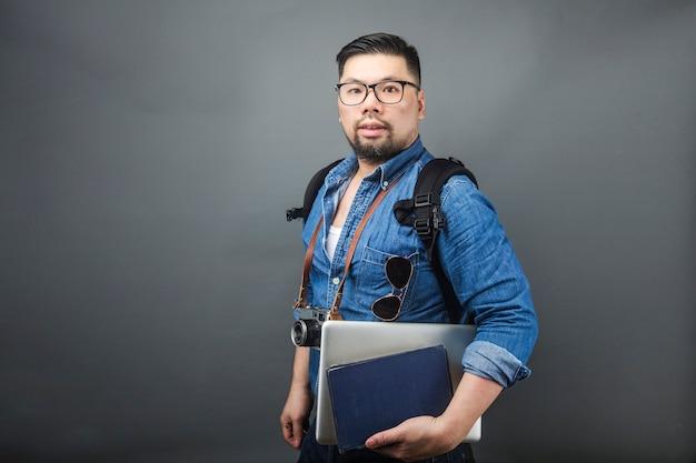 Ein reifer mann trägt seine schultasche und ausrüstung zum reisen.