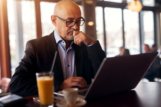 Ein reifer, professioneller, besorgter geschäftsmann überlegt, wie man ein problem löst, während er einen laptop benutzt, der kaffee und saft im café trinkt.
