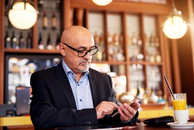 Ein reifer professioneller, ernsthafter geschäftsmann benutzt ein telefon und trinkt kaffee und saft, während er im café sitzt.