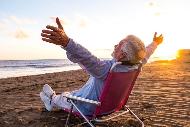 Ein reifer und alter mann, der die sommerferien allein am strand genießt und in einem kleinen stuhl sitzt und auf das meer blickt. männliche person, die sich mit geöffneten armen frei fühlt. freiheit konzept.