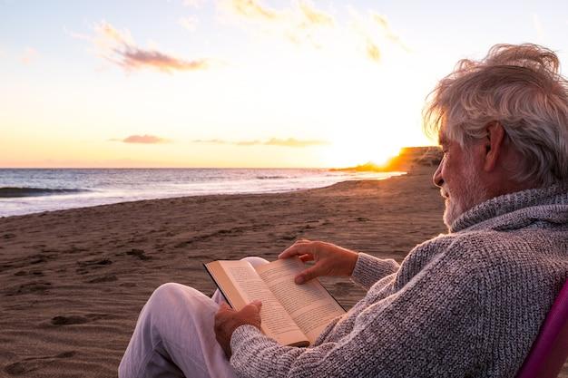 Ein reifer und alter mann, der ein buch liest, das in einem stuhl am strand auf dem sand mit dem sonnenuntergang im hintergrund sitzt. männliche person, die das meer oder den ozean genießt.