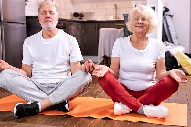 Ein reifes paar sitzt auf dem boden und meditiert in lotus-pose, macht yoga und bleibt mit geschlossenen augen ruhig