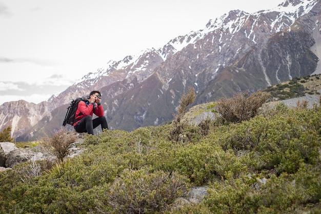 Ein reisender, fotografmann, der foto auf dem berg, schneeberg im hintergrund macht