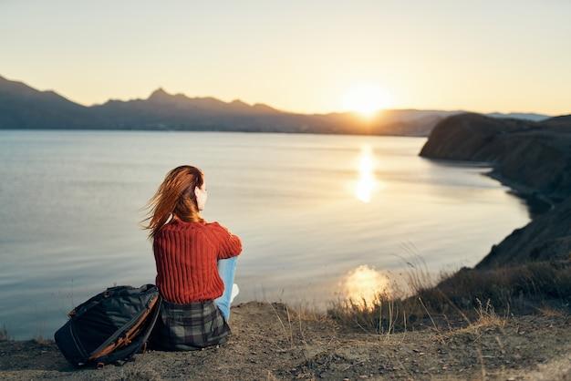 Ein reisender in einem pullover sitzt auf dem boden in den bergen in der nähe des meeres und schaut auf den sonnenuntergang