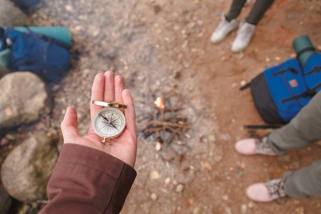 Ein reisender mann hält einen kompass in der hand und steht auf einem steinstrand.