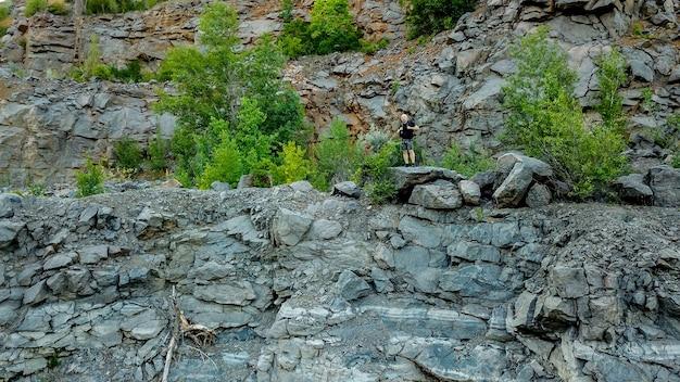 Ein reisender mit einem rucksack auf den schultern steht in der nähe eines klippenbruchs auf dem stein.