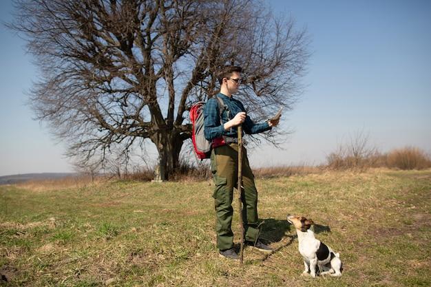 Ein reisender mit einem rucksack und seinem hund, der die karte betrachtet und in die landschaft geht