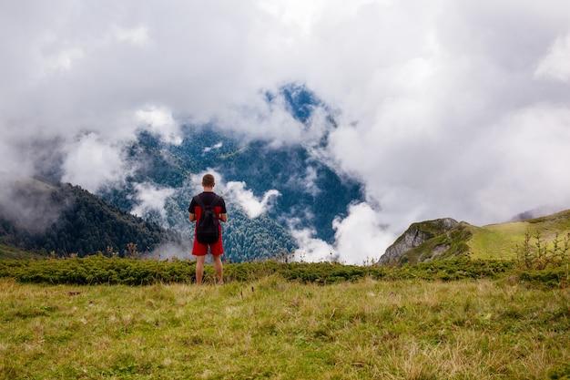 Ein reisender mit rucksack steht hoch in den bergen