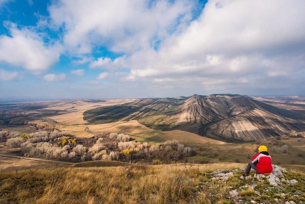 Ein reisender sitzt im herbst auf einem hügel und einem kleinen berg und schaut in die ferne