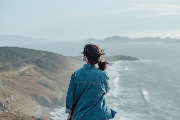 Ein reisender vor der spanischen wildküste, der eine gesichtsmaske, ein wellnesskonzept, leben und freiheit trägt
