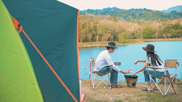 Ein reisendes paar kocht auf dem campingplatz mit blick auf den see und die berge