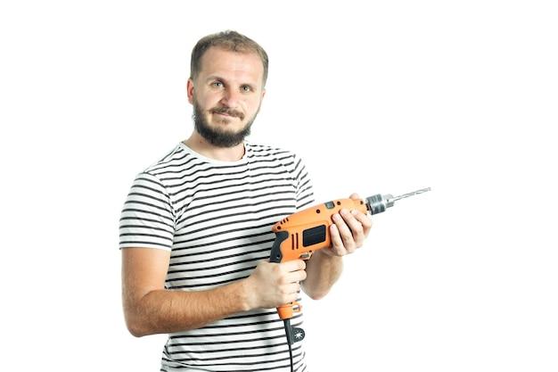Ein resoluter bärtiger mann in einem gestreiften t-shirt hält eine elektrowerkzeug-bohrmaschine in den händen
