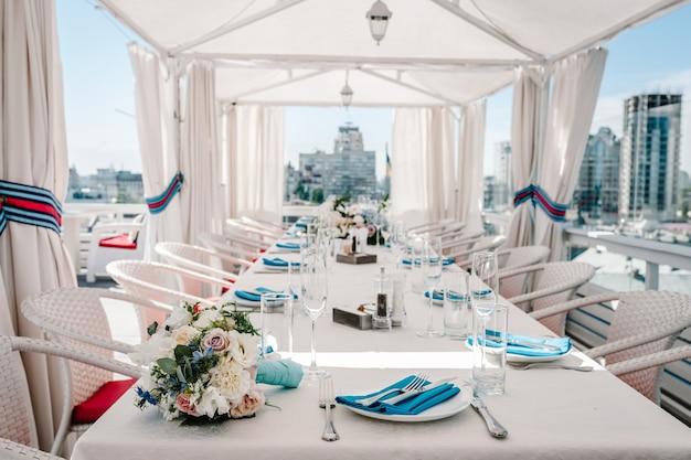 Ein restaurant auf dem dach mit blick auf die stadt. festlicher tisch serviert gerichte und mit blumen dekoriert