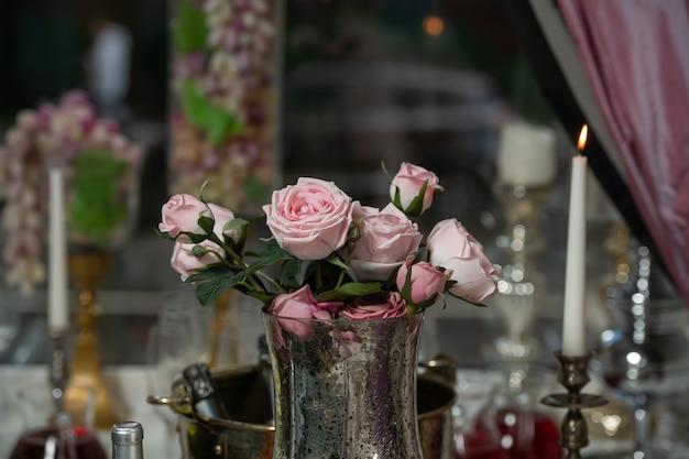 Ein restaurant. auf dem tisch steht eine vase mit rosa rosen. ein romantischer ort.