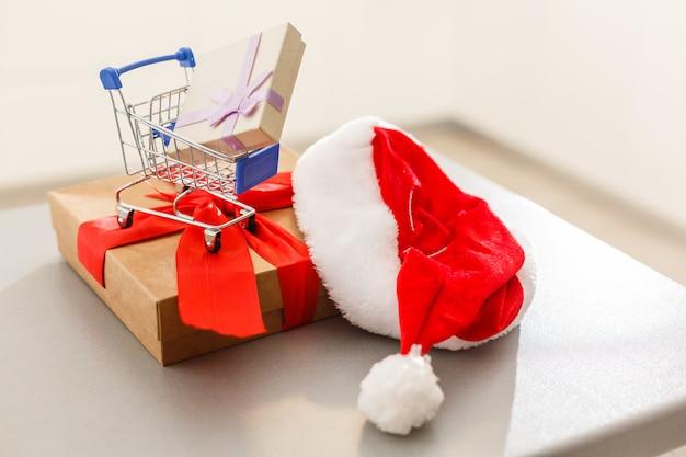 Ein riesiges geschenk mit einem roten band und einem einkaufswagen