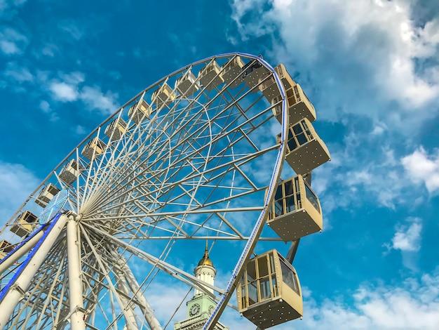 Ein riesiges riesenrad am blauen himmel mit wolken und eine kirche mit einer goldenen kuppel.
