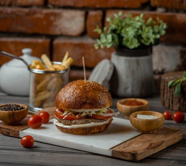 Ein rindfleischburger, gefüllt mit gemüse und vorspeisen, serviert mit kräutern und turshu.