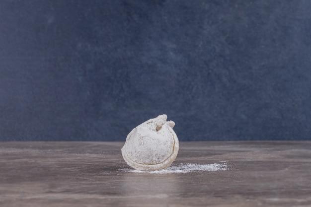 Ein roher knödel auf marmor.