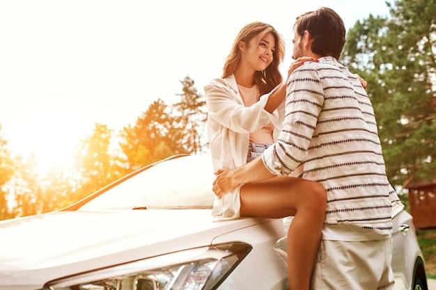 Ein romantisches junges paar umarmt sich in der nähe des autos. camping, wochenende. urlaub, reisen, tourismuskonzept.