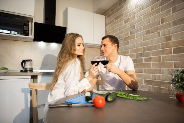 Ein romantisches paar in der küche. mann und frau sitzen am tisch und trinken rotwein. auf dem tisch liegen gurken, tomaten, paprika
