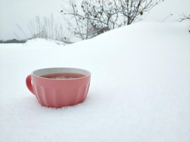 Ein rosa becher mit heißem himbeertee auf dem hintergrund eines schneebedeckten winterfeldes. tee mit marmelade wärmt im kalten winter.
