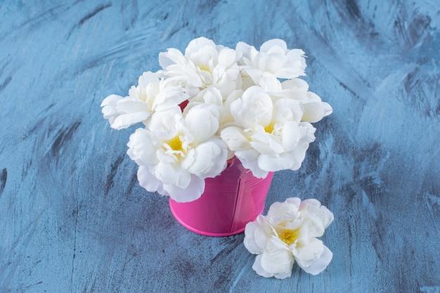 Ein rosa eimer mit schönem weißen blumenstrauß.