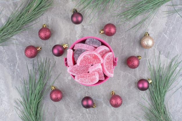 Ein rosa eimer voller süßer marmeladen mit roten weihnachtskugeln auf marmorhintergrund.