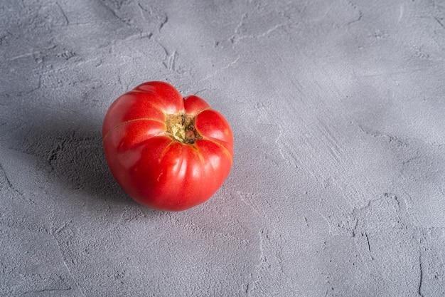 Ein rosa erbstück-tomatengemüse, frische rote reife tomaten, veganes essen, steinbeton, blickwinkel