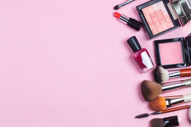 Ein rosa leder bilden beutel mit den kosmetischen schönheitsprodukten, die heraus zu einem pastellbackg verschütten