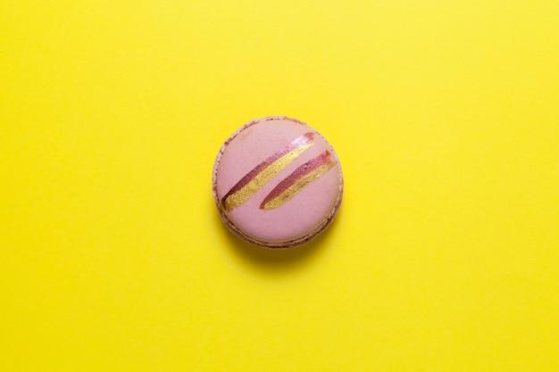 Ein rosa macaron oder eine makrone mit glänzenden goldenen streifen liegt auf gelb