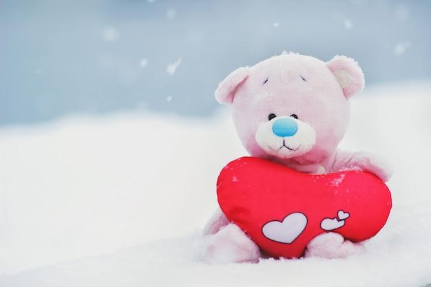 Ein rosa spielzeugbär mit rotem plüschherz sitzt auf dem schnee winterschneetag nahaufnahme