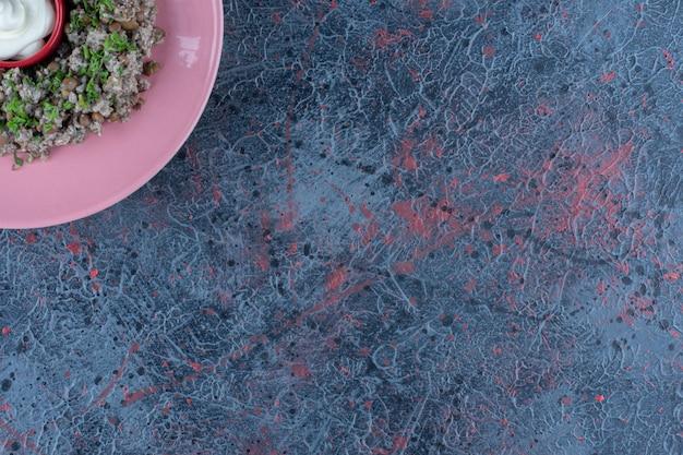 Ein rosa teller hackfleisch mit erbsen und kräutern.