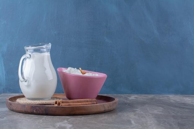 Ein rosa teller mit gesundem haferbrei mit einem glaskrug milch und zimtstangen auf einem holzbrett.