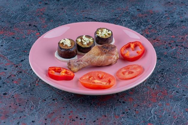 Ein rosa teller mit hühnerbeinfleisch mit geschnittenem gemüse.
