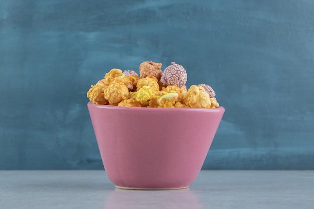 Ein rosa tiefer teller mit süßem mehrfarbigem popcorn.