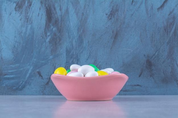 Ein rosa tiefer teller voller bunter bohnenbonbons auf grauem tisch.